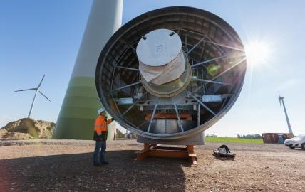 Mann vor dem Generator einer Windkraftanlage