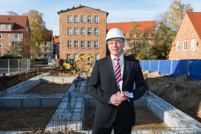 Thomas Pätzold vor dem Grundriss des neuen Verwaltungsgebäudes