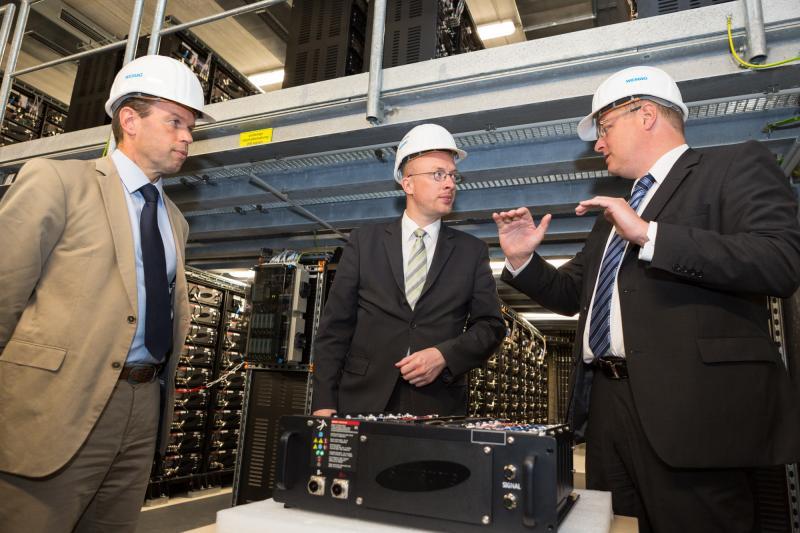 WEMAG-Vorstand Caspar Baumgart, Energieminister Christian Pegel und Projektleiter Tobias Struck im Batteriespeicher