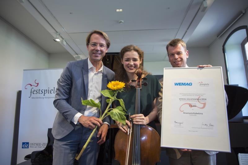 Anastasia Kobekina bekommt den WEMAG-Solistenpreis von Vorstandsmitglied Caspar Baumgart und Festspielintendant Dr. Markus Fein übergeben