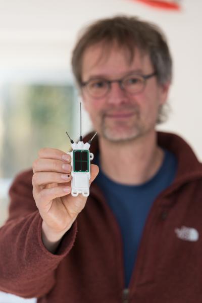 Steffen Hollerbach von der Stork Foundation zeigt den Sender, mit dem der Weißstorch ausgerüstet werden soll.