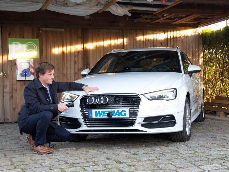 Mann unter seinem Carport mit seinem Audi und einem Nummernschild mit der Aufschrift WEMAG. Im Hintergrund ist die eigene Stromtankstelle zu sehen während er gerade das Kabel anstöpselt