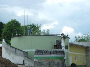 Gebäude zur Biogasförderung mit grünem Anstrich und bewölktem Himmel