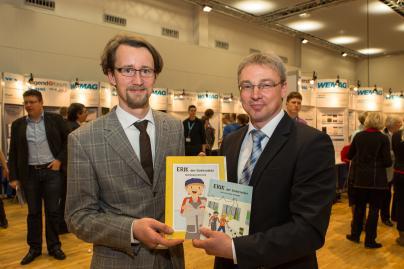 """Bildungsminister Mathias Brodkorb, WEMAG-Vorstand Thomas Pätzold mit dem Buch """"Erik der Elektroniker"""""""