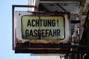 """Altes Schild mit in verblichenem Gelb mit schwarzer ufschrift """"Achtung! Gasgefahr"""