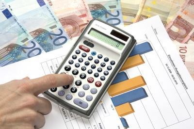 Ein Taschenrechner mit der Zahl 0 und einem Finger auf den Zahlen um etwas einzutippen. Unter dem taschenrechner liegt ein Blatt mit Diagrammen und darunter Geldscheine in Höhe von 10 und 20 €.