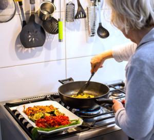 Eine ältere Frau kocht und brät über einem Gasherd