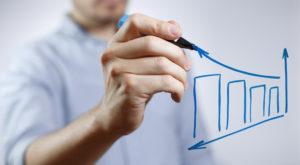 Mann in blauem Hemd der eine steigende Kurve zeichnet