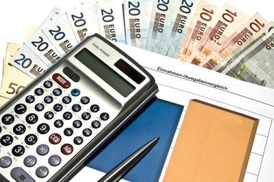 Taschenrchner mit einem Datenblatt darunter sowie Geldscheinen von 5 bis 50 €