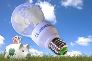 Energiesparlampe sowie ein Sparschwein mit € Scheinen die raus gucken. Blauer Himmel und grüne Wiese die für ökologisches Handeln stehen